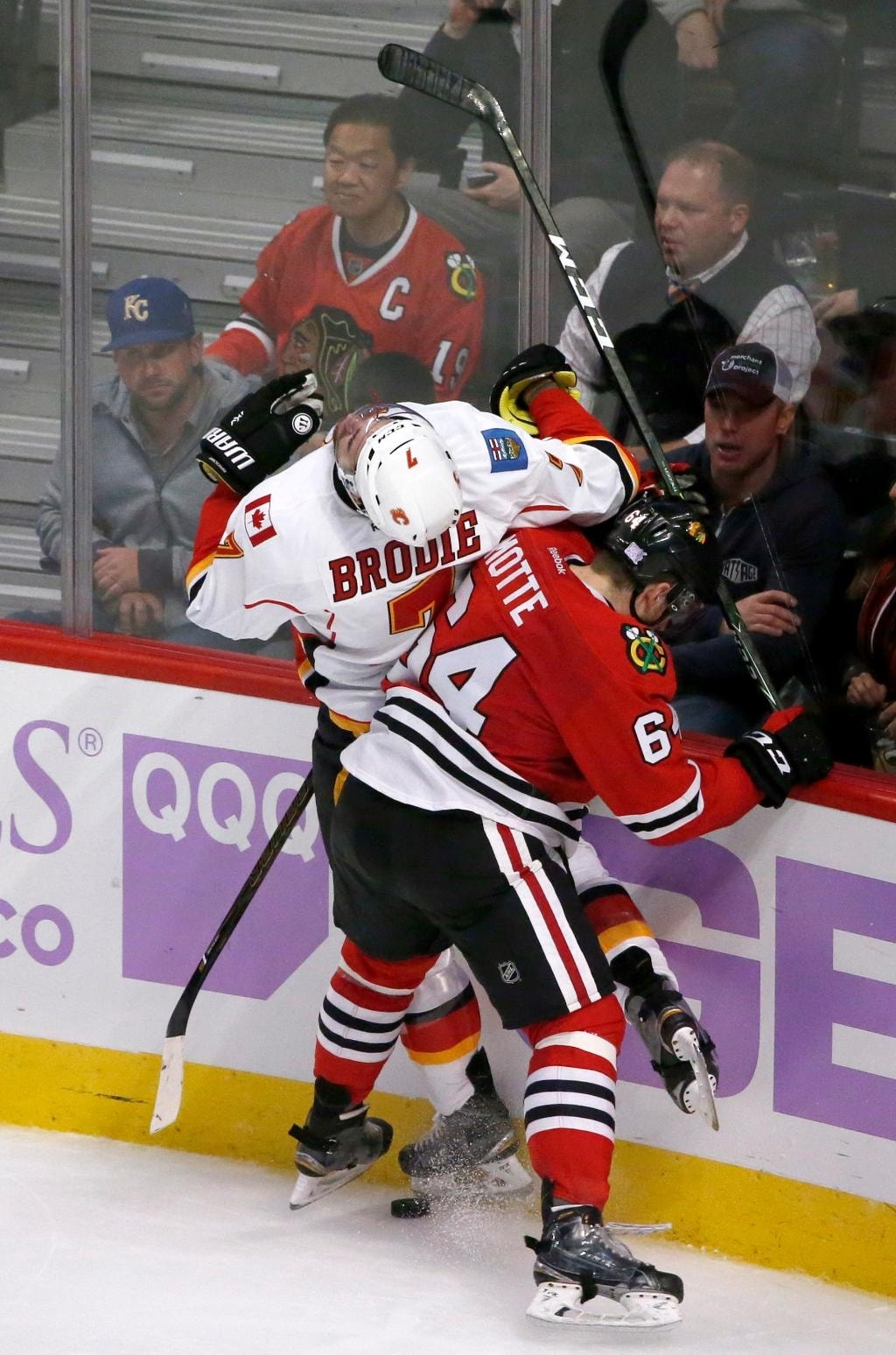 Chicago Blackhawks' Tyler Motte (64) checks Calgary Flames' TJ Brodie into the boards and is called for a four minute high sticking penalty during the second period of an NHL hockey game, Monday, Oct. 24, 2016, in Chicago. (AP Photo/Charles Rex Arbogast)