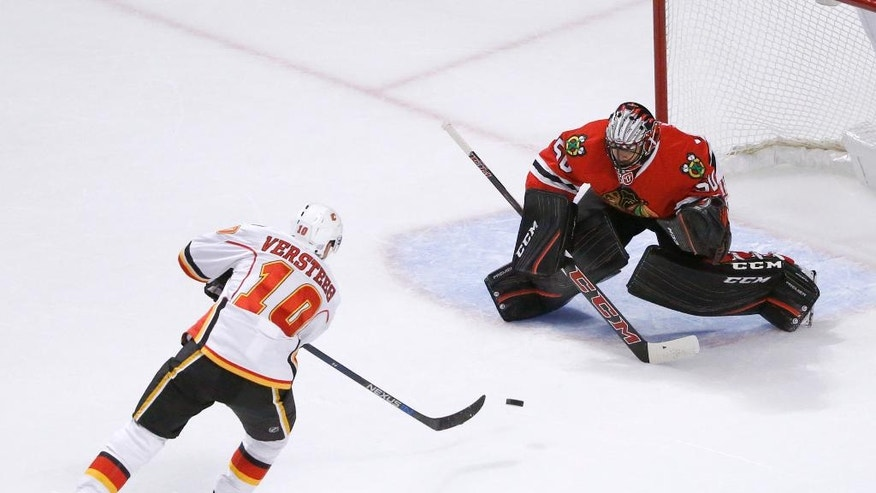 Calgary Flames' Kris Versteeg (10) takes a shot on goal as Chicago Blackhawks goalie Corey Crawford makes the save during the first period of an NHL hockey game Monday, Oct. 24, 2016, in Chicago. (AP Photo/Charles Rex Arbogast)