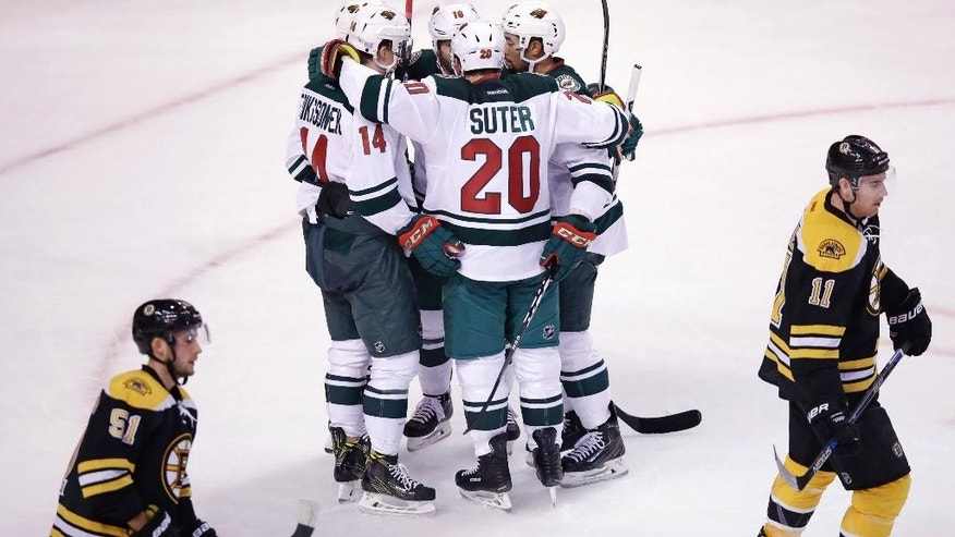 Minnesota Wild right wing Jason Pominville is surrounded by teammates after his goal during the third period of a hockey game against the Boston Bruins in Boston, Tuesday, Oct. 25, 2016. The Wild shut out the Bruins 5-0. (AP Photo/Charles Krupa)