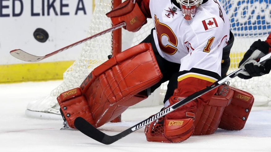 Calgary Flames goalie Brian Elliott keeps his eye on a loose puck during the second period of an NHL hockey game against the St. Louis Blues Tuesday, Oct. 25, 2016, in St. Louis. (AP Photo/Jeff Roberson)