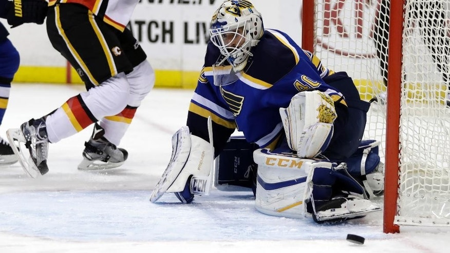 St. Louis Blues goalie Carter Hutton, right, deflects a puck as Calgary Flames' Matthew Tkachuk watches during the first period of an NHL hockey game Tuesday, Oct. 25, 2016, in St. Louis. (AP Photo/Jeff Roberson)
