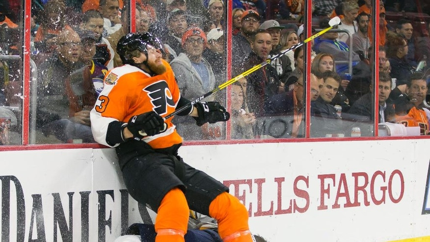 Philadelphia Flyers' Jakub Voracek, top, goes into the boards with Buffalo Sabres' Zemgus Girgensons, bottom, beneath him during the second period of an NHL hockey game, Tuesday, Oct. 25, 2016, in Philadelphia. (AP Photo/Chris Szagola)