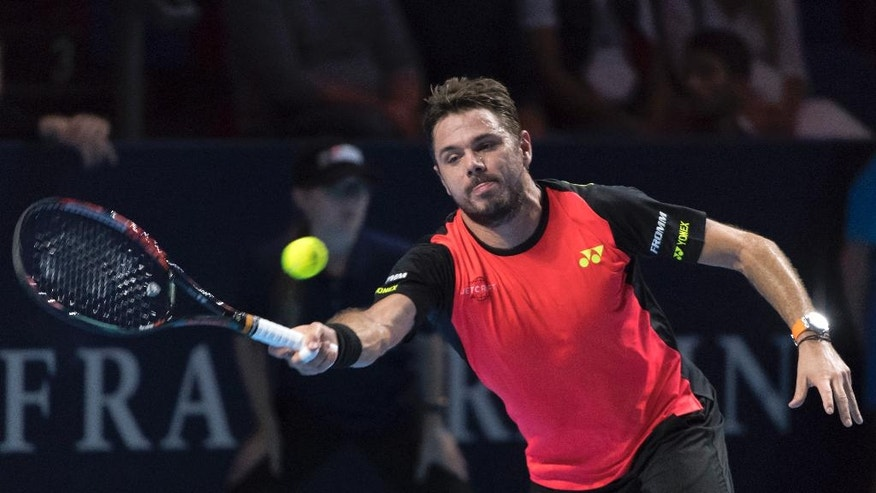Switzerland's Stan Wawrinka returns a ball to Switzerland's Marco Chiudinelli during their first round match, during the Swiss Indoors tennis tournament, at the St. Jakobshalle in Basel, Switzerland, on Tuesday, Oct. 25, 2016. (Georgios Kefalas/Keystone via AP)