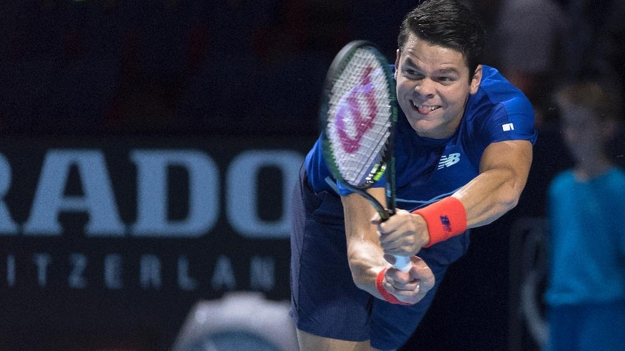 Canada's Milos Raonic returns a ball to Lithuania's Ricardas Berankis during their first round match at the Swiss Indoors tennis tournament at the St. Jakobshalle in Basel, Switzerland, on Tuesday, Oct. 25, 2016.  (Georgios Kefalas/Keystone via AP)
