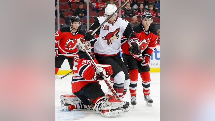Arizona Coyotes center Martin Hanzal (11) collides with New Jersey Devils goalie Cory Schneider (35) during the first period of an NHL hockey game, Tuesday, Oct. 25, 2016, in Newark, N.J. (AP Photo/Julie Jacobson)