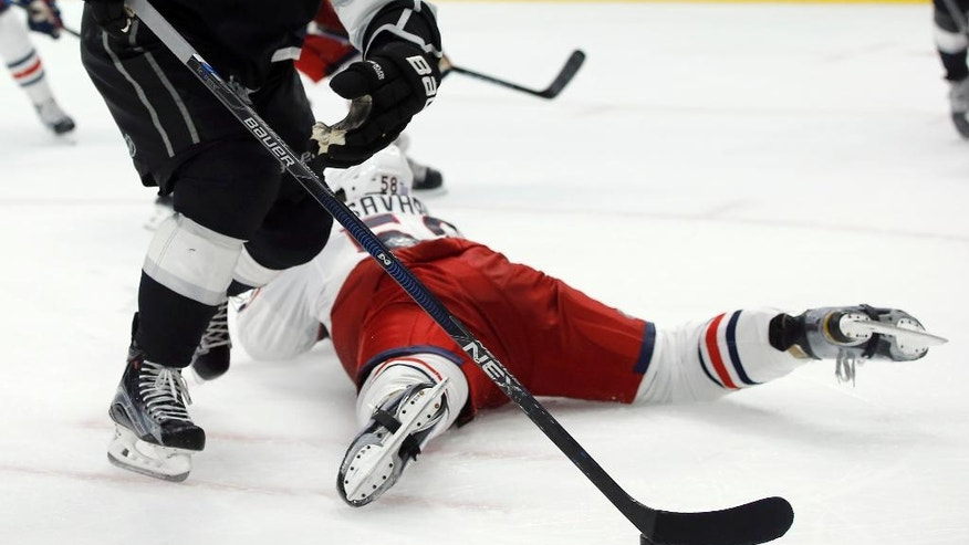 Los Angeles Kings center Anze Kopitar, left, of Slovenia, skates around Columbus Blue Jackets defenseman David Savard, below, with the puck during the second period of an NHL hockey game in Los Angeles, Tuesday, Oct. 25, 2016. (AP Photo/Alex Gallardo)