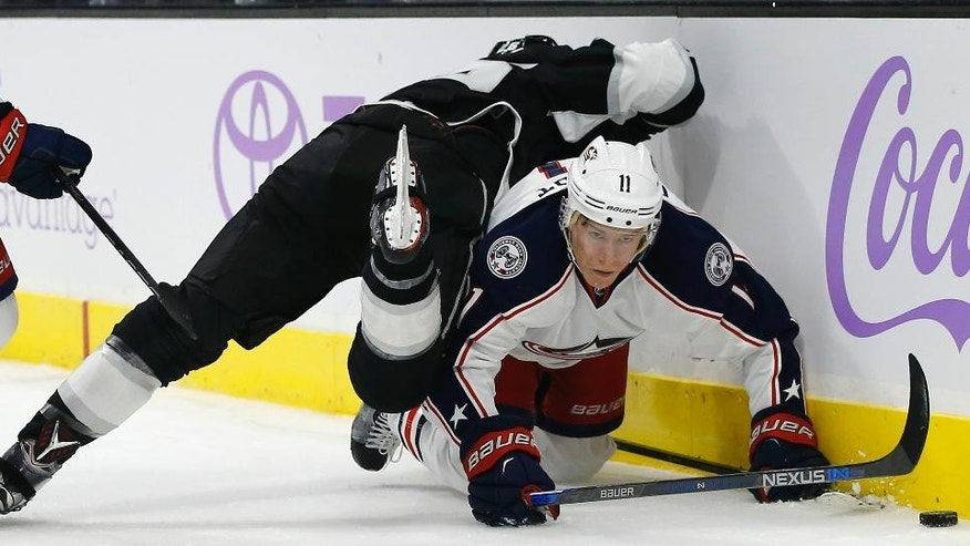Los Angeles Kings center Nic Dowd, top, lands on Columbus Blue Jackets left wing Matt Calvert, right, during the first period of an NHL hockey game in Los Angeles, Tuesday, Oct. 25, 2016. (AP Photo/Alex Gallardo)