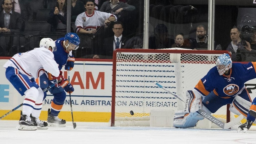 Montreal Canadiens left wing Paul Byron, left, scores a goal past New York Islanders defenseman Travis Hamonic, second from left, and goalie Thomas Greiss during the second period of an NHL hockey game Wednesday, Oct. 26, 2016 in New York. (AP Photo/Mary Altaffer)