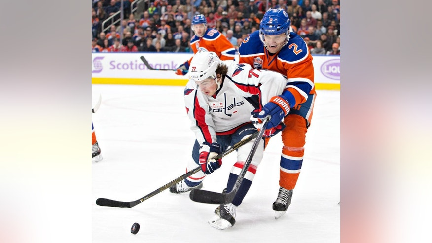 Washington Capitals' T.J. Oshie (77) battles for the puck with Edmonton Oilers' Andrej Sekera (2) during the first period of an NHL hockey game in Edmonton, Alberta, Wednesday, Oct. 26, 2016. (Jason Franson/The Canadian Press via AP)