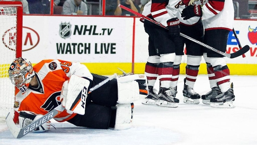 Philadelphia Flyers goalie Steve Mason looks back for the puck as the Arizona Coyotes' from the left, Anthony Duclair, Jamie McGinn and Connor Murphy celebrate McGinn's goal during the first period of an NHL hockey game, Thursday, Oct. 27, 2016, in Philadelphia. (AP Photo/Tom Mihalek)