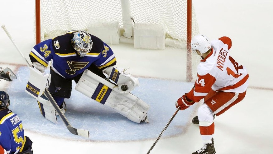 St. Louis Blues goalie Jake Allen (34) gloves the puck as Detroit Red Wings' Gustav Nyquist, of Sweden, watches during the second period of an NHL hockey game Thursday, Oct. 27, 2016, in St. Louis. (AP Photo/Jeff Roberson)