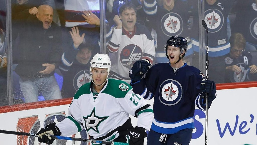 Winnipeg Jets' Kyle Connor (81) celebrates his first NHL goal as Dallas Stars' Adam Cracknell (27) looks on during the first period of an NHL hockey game in Winnipeg, Manitoba, Thursday, Oct. 27, 2016. (John Woods/The Canadian Press via AP)