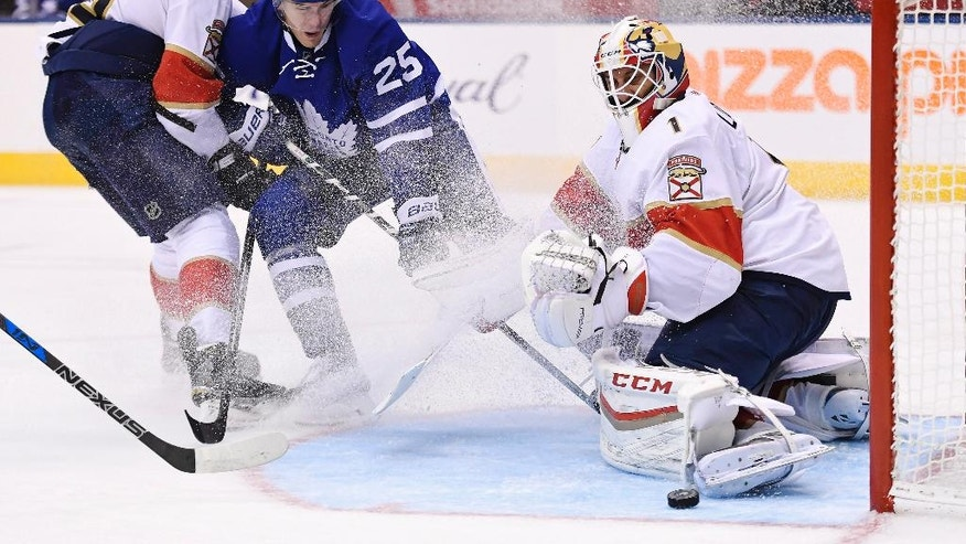 Florida Panthers goalie Roberto Luongo (1) makes a save as Florida Panthers defenseman Alex Petrovic (6) and Toronto Maple Leafs left wing James van Riemsdyk (25) battle during the second period of an NHL hockey game in Toronto on Thursday, Oct. 27, 2016. (Frank Gunn/The Canadian Press via AP)