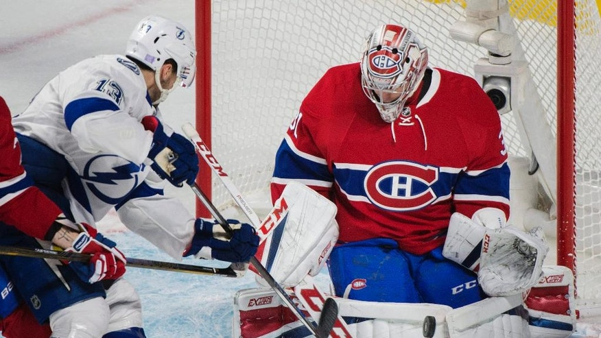 Montreal Canadiens goaltender Carey Price makes a save against Tampa Bay Lightning's Cedric Paquette (13) during the first period of an NHL hockey game in Montreal on Thursday, Oct. 27, 2016. (Graham Hughes/The Canadian Press via AP)