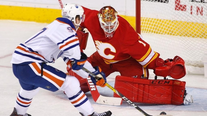 FILE - In this Oct. 14, 2016, file photo, Edmonton Oilers' Connor McDavid, left, scores against Calgary Flames goalie Brian Elliott during first-period NHL hockey game action in Calgary, Alberta.  McDavid leads the NHL with 11 points. (Larry MacDougal/The Canadian Press via AP, File)