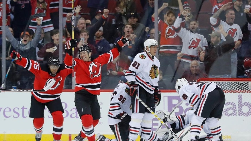 New Jersey Devils right wing PA Parenteau, second from left, and right wing Devante Smith-Pelly (25) react after Parenteau scored a goal against the Chicago Blackhawks during the first period of an NHL hockey game, Friday, Oct. 28, 2016, in Newark, N.J. (AP Photo/Julie Jacobson)