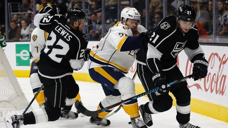 Los Angeles Kings center Nick Shore, right, controls the puck against Nashville Predators defenseman Matt Irwin, center, with center Trevor Lewis (22) during the second period of an NHL hockey game in Los Angeles, Thursday, Oct. 27, 2016. (AP Photo/Alex Gallardo)