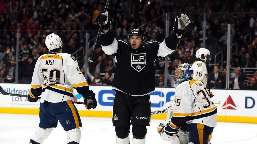 Los Angeles Kings right wing Dustin Brown, center, celebrates a goal, against Nashville Predators defenseman Roman Josi, left, of Switzerland, and goalie Pekka Rinne, right, of Finland, and during the second period of an NHL hockey game in Los Angeles, Thursday, Oct. 27, 2016. (AP Photo/Alex Gallardo)