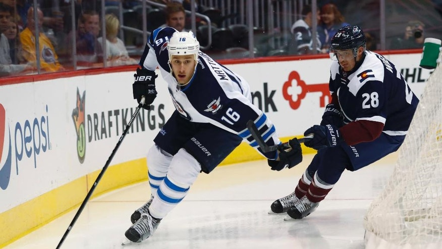 Winnipeg Jets center Shawn Matthias, left, drives around the net for a shot with Colorado Avalanche defenseman Patrick Wiercioch in pursuit in the second period of an NHL hockey game Friday, Oct. 28, 2016, in Denver. (AP Photo/David Zalubowski)