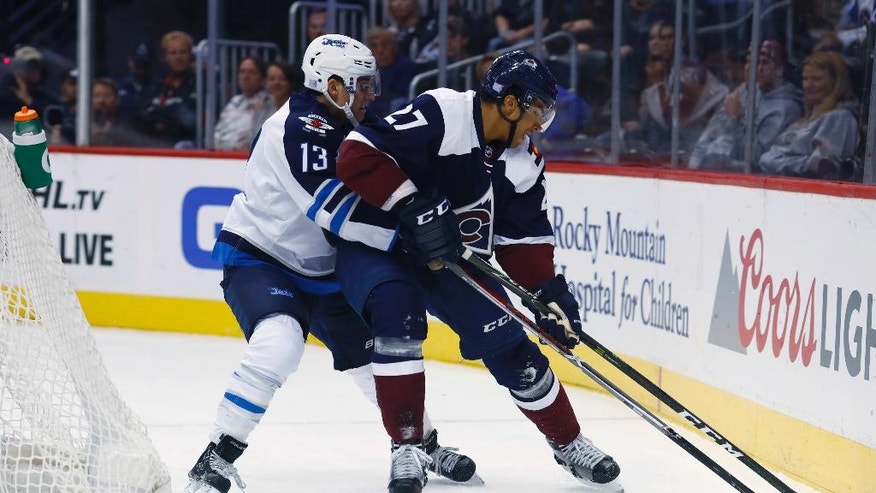 Winnipeg Jets left wing Brandon Tanev, left, and Colorado Avalanche left wing Andreas Martinsen, of Norway, try to control the puck during the first period of an NHL hockey game Friday, Oct. 28, 2016, in Denver. (AP Photo/David Zalubowski)