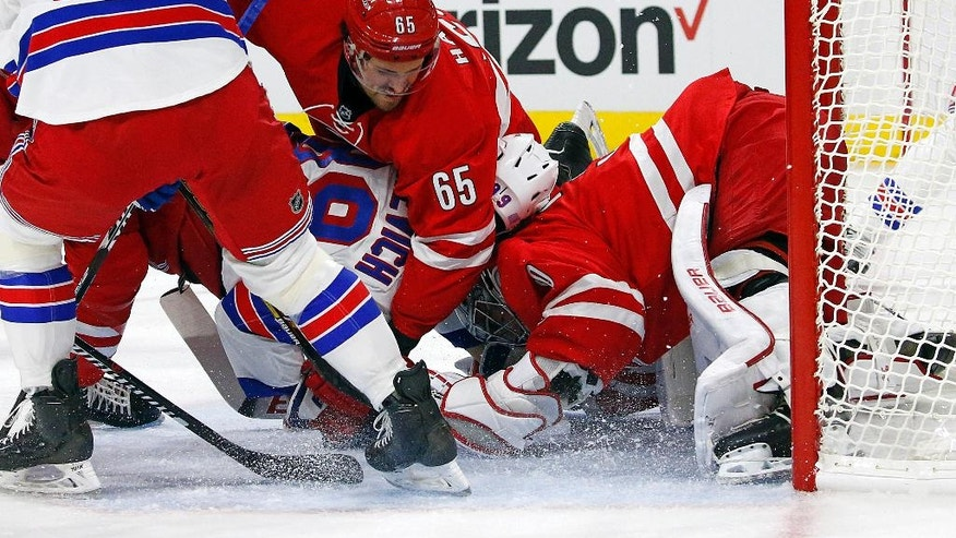 New York Rangers' Pavel Buchnevich gets sandwiched between Carolina Hurricanes goalie Cam Ward (30) and Hurricanes' Ron Hainsey (65) during the first period of an NHL hockey game, Friday, Oct. 28, 2016, in Raleigh, N.C. (AP Photo/Karl B DeBlaker)