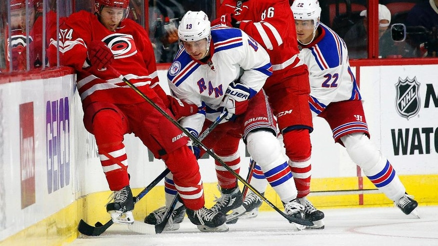 Carolina Hurricanes' Jaccob Slavin (74) works against New York Rangers' Jesper Fast (19) with Hurricanes' Teuvo Teravainen (86) and Rangers' Nick Holden (22) nearby during the first period of an NHL hockey game, Friday, Oct. 28, 2016, in Raleigh, N.C. (AP Photo/Karl B DeBlaker)