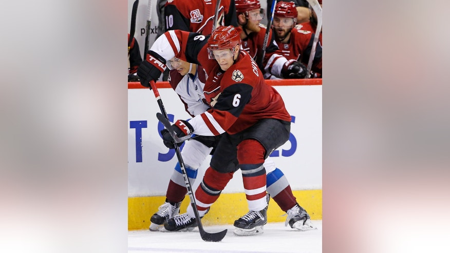Arizona Coyotes defenseman Jakob Chychrun (6) keeps the puck away from Colorado Avalanche right wing Rene Bourque during the first period of an NHL hockey game Saturday, Oct. 29, 2016, in Glendale, Ariz. (AP Photo/Ross D. Franklin)