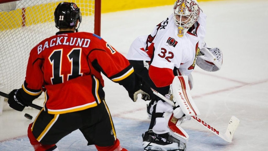 Ottawa Senators goalie Chris Driedger, right, looks back as Calgary Flames' Mikael Backlund, from Sweden, watches a goal by Michael Frolik, from the Czech Republic, during the third period of an NHL hockey game Friday, Oct. 28, 2016, in Calgary, Alberta. (Jeff McIntosh/The Canadian Press via AP)