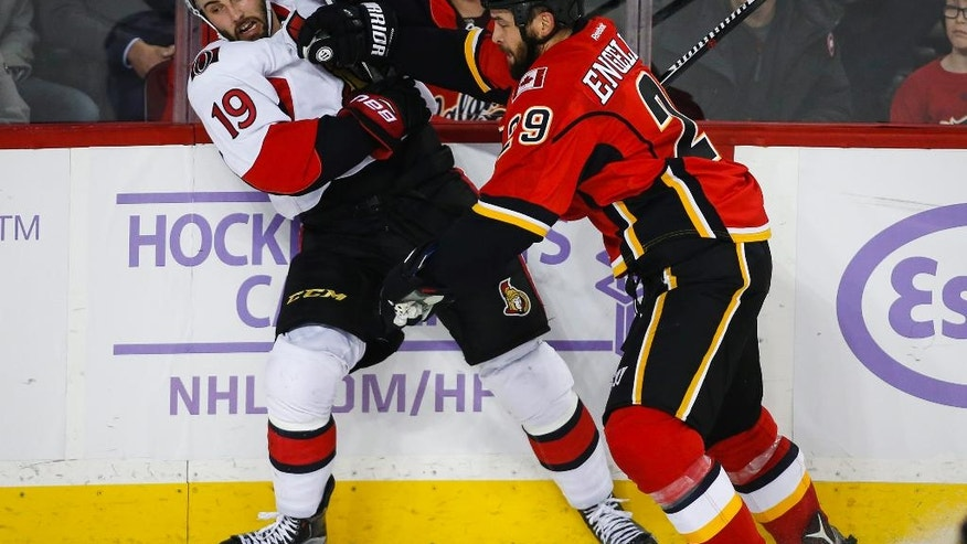 Ottawa Senators' Derick Brassard, left, tangles with Calgary Flames' Deryk Engelland during the second period of an NHL hockey game Friday, Oct. 28, 2016, in Calgary, Alberta. (Jeff McIntosh/The Canadian Press via AP)