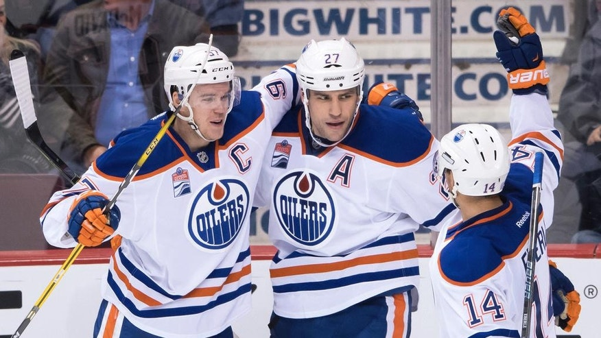 Edmonton Oilers' Connor McDavid, Milan Lucic and Jordan Eberle, from left, celebrate Lucic's empty-net goal against the Vancouver Canucks during the third period of an NHL hockey game Friday, Oct. 28, 2016, in Vancouver, British Columbia. (Darryl Dyck/The Canadian Press via AP)