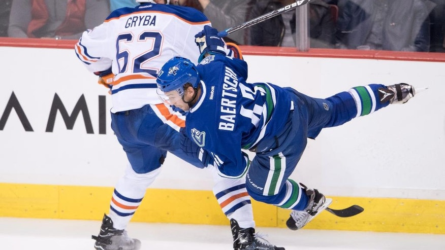 Edmonton Oilers' Eric Gryba, left, checks Vancouver Canucks' Sven Baertschi during the third period of an NHL hockey game Friday, Oct. 28, 2016, in Vancouver, British Columbia. (Darryl Dyck/The Canadian Press via AP)