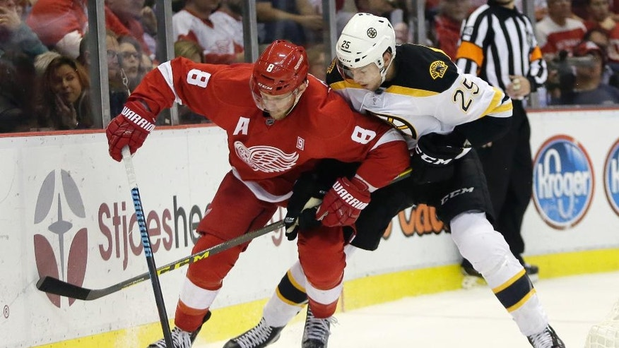 Detroit Red Wings left wing Justin Abdelkader (8) tries to maintain control of the puck against Boston Bruins defenseman Brandon Carlo (25) during the second period of an NHL hockey game Saturday, Oct. 29, 2016, in Detroit. (AP Photo/Duane Burleson)
