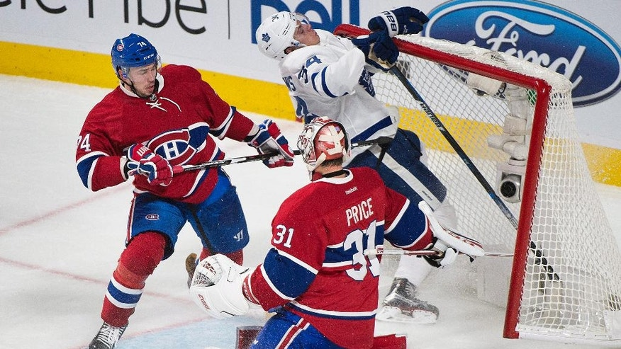 Toronto Maple Leafs' Auston Matthews (34) collides with the net of Montreal Canadiens goaltender Carey Price as Canadiens' Alexei Emelin (74) defends during first period NHL hockey action in Montreal, Saturday, Oct. 29, 2016. (Graham Hughes/The Canadian Press via AP)