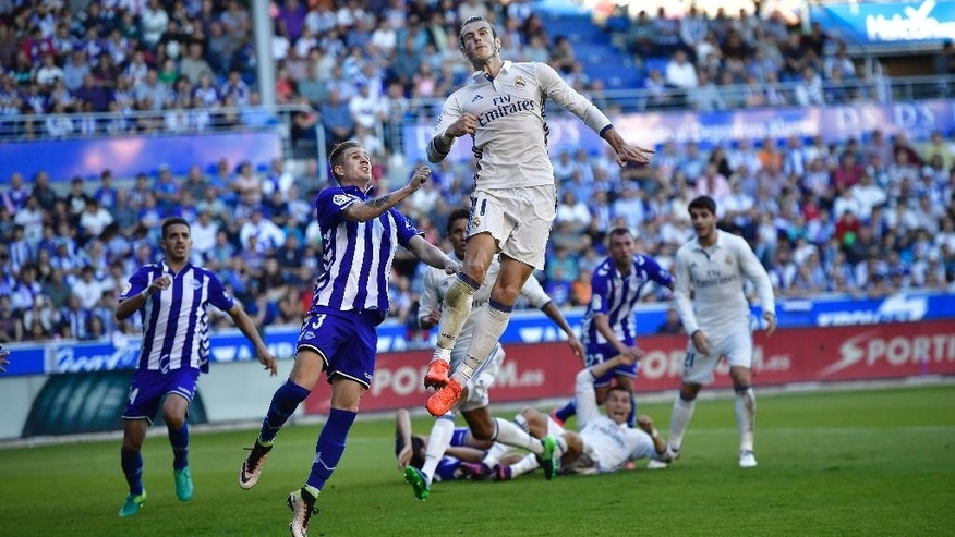 Real Madrid's Gareth Bale, jumps for the ball beside Deportivo Alaves Raul Garcia during the Spanish La Liga soccer match between Real Madrid and Deportivo Alaves, at Mendizorroza stadium, in Vitoria, northern Spain, Saturday, Oct. 29, 2016. (AP Photo/Alvaro Barrie