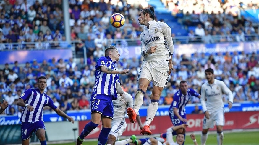 Real Madrid's Gareth Bale, jumps for the ball beside Deportivo Alaves Raul Garcia during the Spanish La Liga soccer match between Real Madrid and Deportivo Alaves, at Mendizorroza stadium, in Vitoria, northern Spain, Saturday, Oct. 29, 2016. (AP Photo/Alvaro Barrientos)