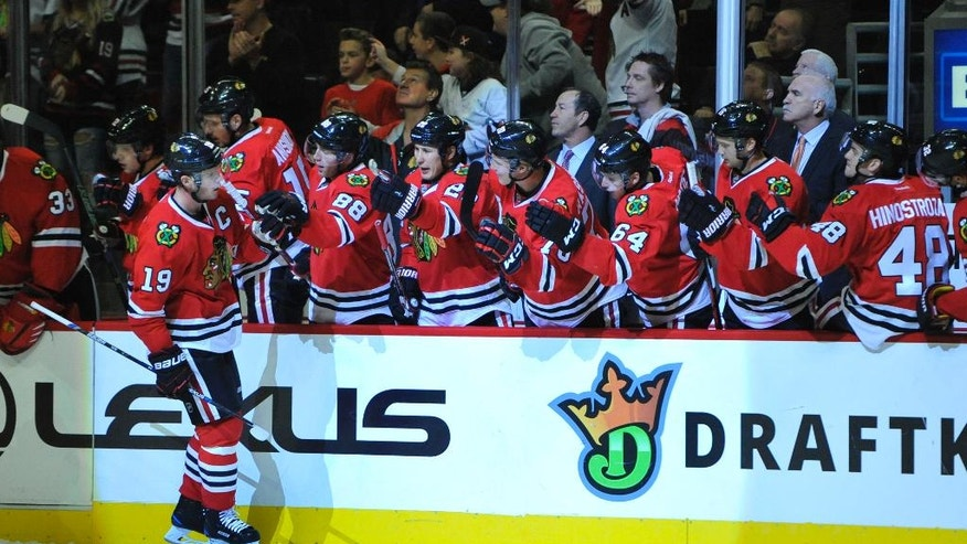 Chicago Blackhawks' Jonathan Toews (19) celebrates with teammates on the bench after scoring a goal during the first period of a hockey game against the Los Angeles Kings Sunday, Oct. 30, 2016, in Chicago. (AP Photo/Paul Beaty)
