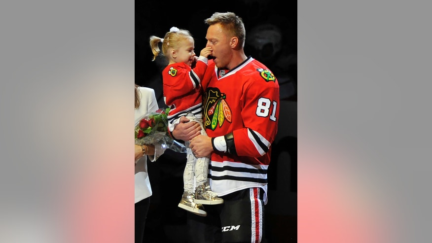 Chicago Blackhawks' Marian Hossa of Slovakia, jokes with daughter Zoja while being honored by the Blackhawks for scoring 500 career goals before a hockey game against the Los Angeles Kings Sunday, Oct. 30, 2016, in Chicago. (AP Photo/Paul Beaty)