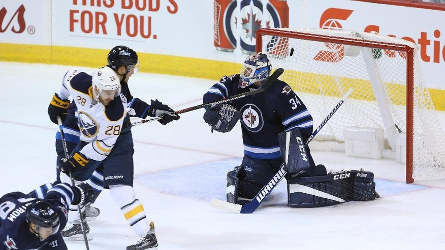 A shot from Buffalo Sabres forward Kyle Okposo (not shown) beats Winnipeg Jets goaltender Michael Hutchinson (34) as Sabres forward Zemgus Girgensons (28), of Latvia, and Jets defenceman Ben Chiarot (7) battle in front of the net during first-period NHL hockey game action in Winnipeg, Manitoba, Sunday, Oct. 30, 2016. (Jason Halstead/The Canadian Press via AP)