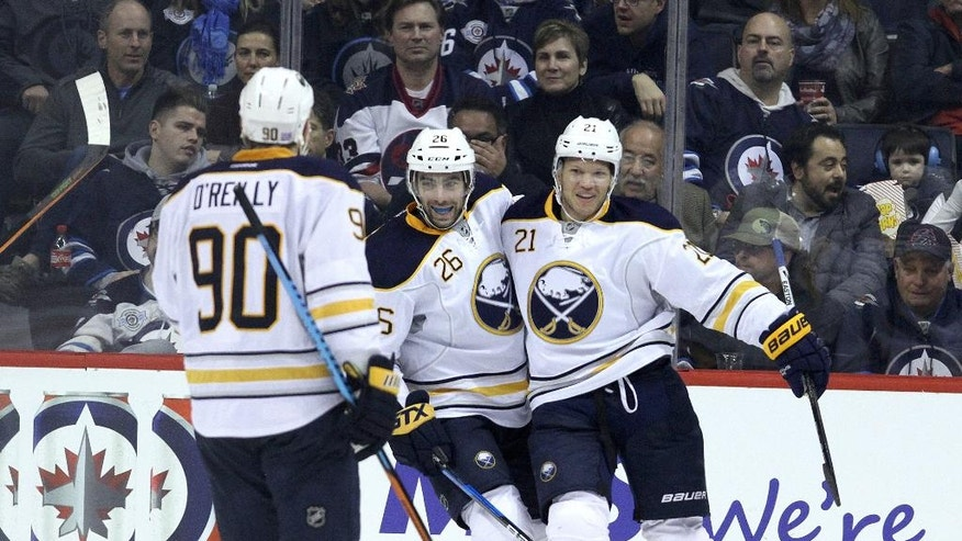 Buffalo Sabres forwards Kyle Okposo (21), Matt Moulson (26) and Ryan O'Reilly (90) celebrate Okposo's goal on Winnipeg Jets goaltender Michael Hutchinson during second period NHL hockey action in Winnipeg, Manitoba, Sunday, Oct. 30, 2016. (Jason Halstead/The Canadian Press via AP)