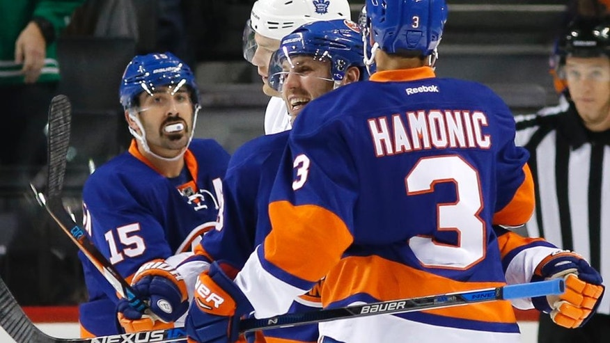 New York Islanders right wing Cal Clutterbuck (15) watches as center Casey Cizikas, center, and defenseman Travis Hamonic (3) celebrate after Hamonic scored a goal during the first period of an NHL hockey game against the Toronto Maple Leafs, Sunday, Oct. 30, 2016, in New York. (AP Photo/Kathy Willens)