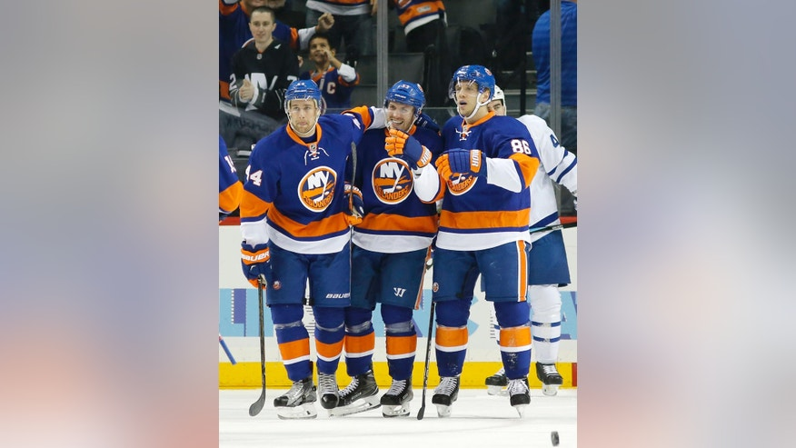 New York Islanders defenseman Calvin de Haan (44), Casey Cizikas, (53) and left wing Nikolay Kulemin (86) celebrate after Cizikas scored a goal during the first period of an NHL hockey game against Toronto Maple Leafs, Sunday, Oct. 30, 2016, in New York. (AP Photo/Kathy Willens)