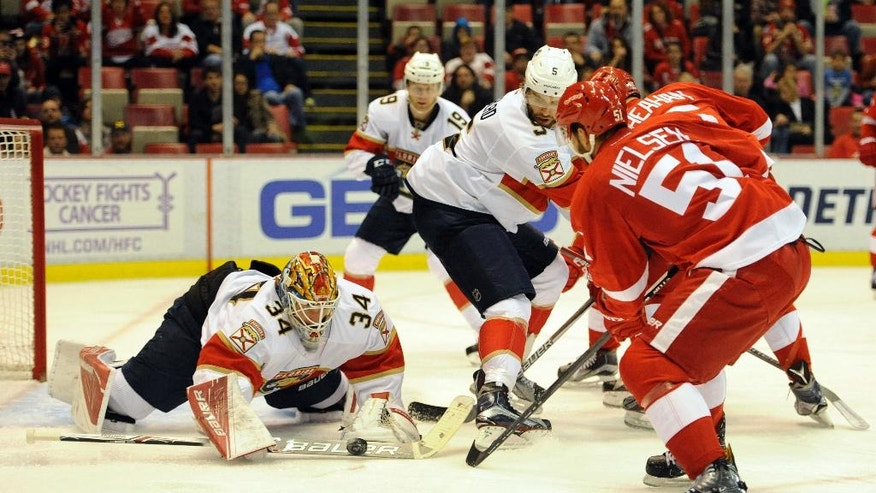 Florida Panthers goalie James Reimer (34) makes the save as Detroit Red Wings center Frans Nielsen (51), of Denmark, moves in for the rebound in the second period of an NHL hockey game in Detroit, Sunday, Oct. 30, 2016. (AP Photo/Jose Juarez)
