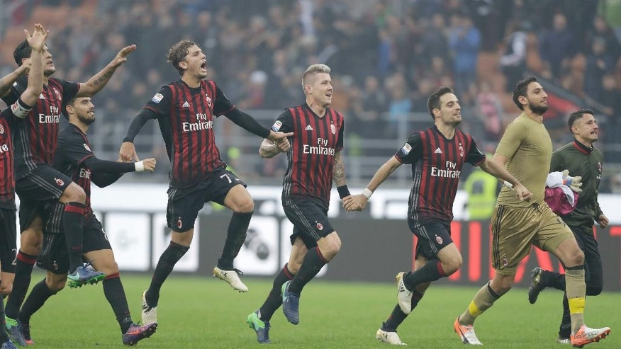 AC Milan's players celebrate their 1-0 win over Pescara at the end of a Serie A soccer match at the San Siro stadium in Milan, Italy, Sunday, Oct. 30, 2016.  (AP Photo/Luca Bruno)