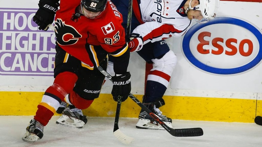 Washington Capitals' Lars Eller, right, from Denmark, battles Calgary Flames' Sam Bennett, for the puck during second period NHL hockey action in Calgary, Alberta, Sunday, Oct. 30, 2016. (Jeff McIntosh/The Canadian Press via AP)