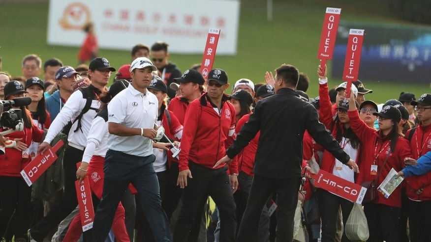 Japan's Hideki Matsuyama walks on the fairway as the crowd surge forward on the 18th hole during the 2016 WGC-HSBC Champions golf tournament at the Sheshan International Golf Club in Shanghai, China, Sunday, Oct. 30, 2016. (AP Photo/Ng Han Guan)