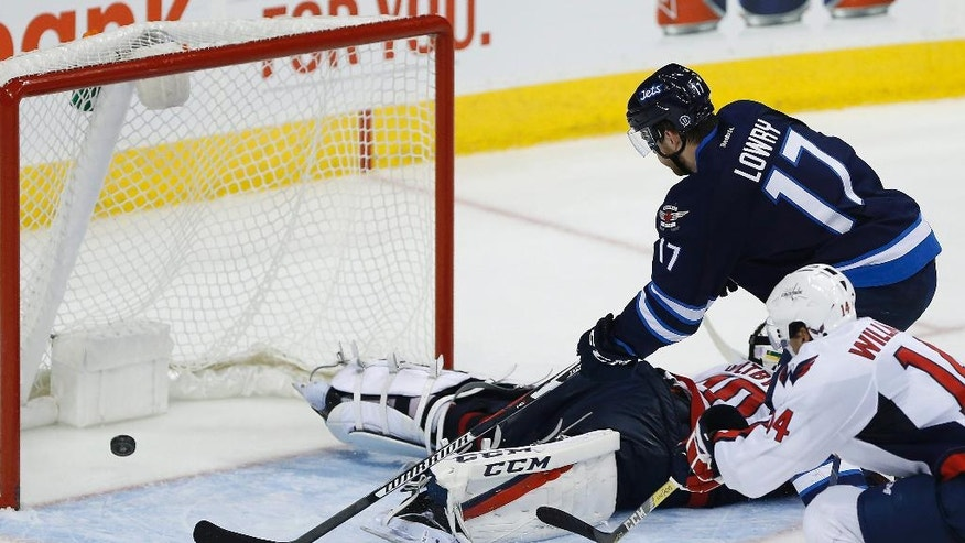 Winnipeg Jets' Adam Lowry (17) scores the tying goal against Washington Capitals goaltender Braden Holtby (70) as Justin Williams (14) defends during the third period of an NHL hockey game Tuesday, Nov. 1, 2016, in Winnipeg, Manitoba. (John Woods/The Canadian Press via AP)