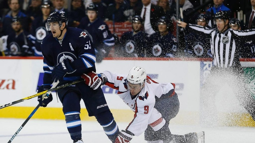 Washington Capitals' Dmitry Orlov (9) attempts to stop Winnipeg Jets' Mark Scheifele (55) during the second period of an NHL hockey game Tuesday, Nov. 1, 2016, in Winnipeg, Manitoba. (John Woods/The Canadian Press via AP)