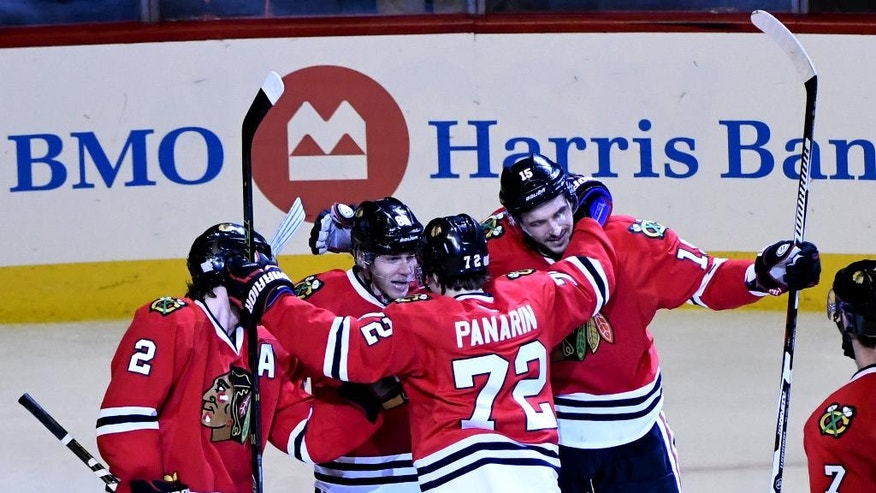 Chicago Blackhawks' Duncan Keith (2), Patrick Kane, second from left, Artemi Panarin (72) and Artem Anisimov, right, celebrate Anisimov's goal during the third period of an NHL hockey game against the Calgary Flames on Tuesday Nov. 1, 2016, in Chicago. The Chicago Blackhawks beat the Calgary Flames 5-1. (AP Photo/Matt Marton)