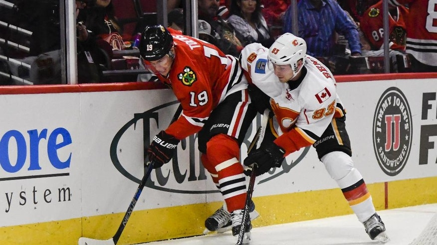 Chicago Blackhawks Jonathan Toews, left, shields the puck from Calgary Flames' Sam Bennett during the first period of an NHL hockey game, Tuesday Nov. 1, 2016, in Chicago. (AP Photo/Matt Marton)