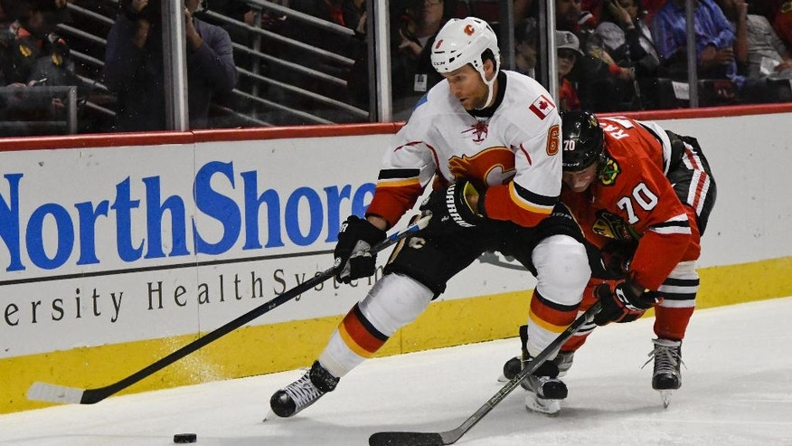 Calgary Flames' Dennis Wideman (6) and Chicago Blackhawks' Dennis Rasmussen (70) battle for the puck during the first period of an NHL hockey game between the Chicago Blackhawks and the Calgary Flames on Tuesday Nov. 1, 2016, in Chicago. (AP Photo/Matt Marton)